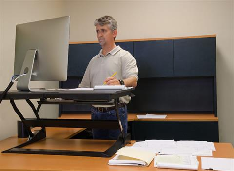 Man using a standing desk from Specialized Office Systems