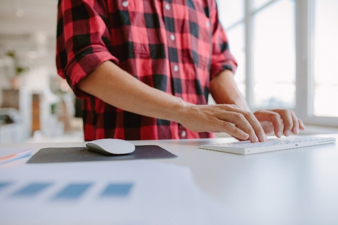 man typing at sit to stand desk
